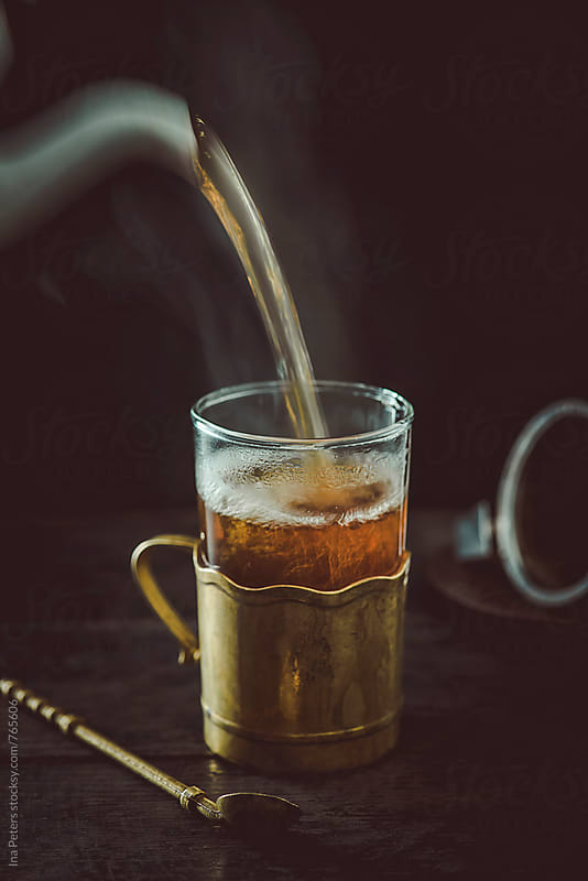 Drink: Black Tea being poured into a glass cup by Ina Peters for Stocksy United