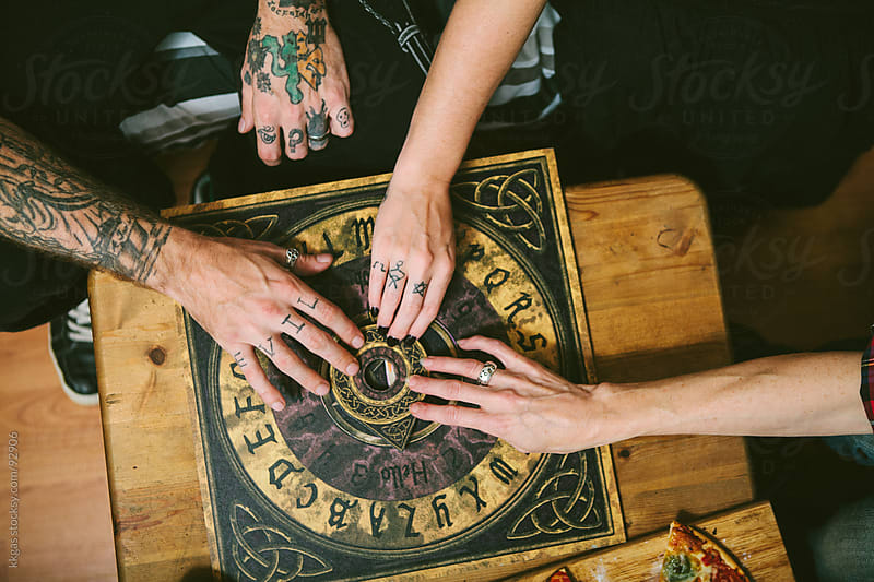 group of friends experimenting with a Ouija board at Halloween by kkgas for Stocksy United