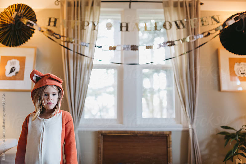 Little girl in fox costume staring blankly by Rob and Julia Campbell for Stocksy United