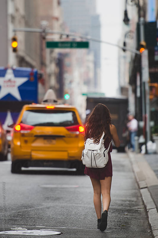 Young woman walking in street in the city by Lauren Naefe for Stocksy United
