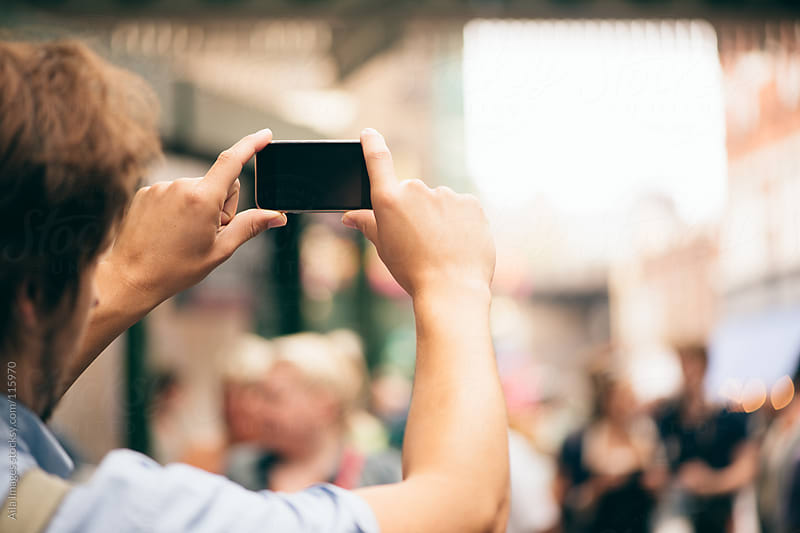 Man taking photograph on his phone by Aila Images for Stocksy United