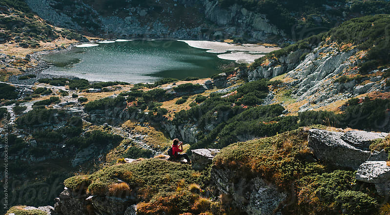Curly man taking photos in nature by Marko Milovanović for Stocksy United