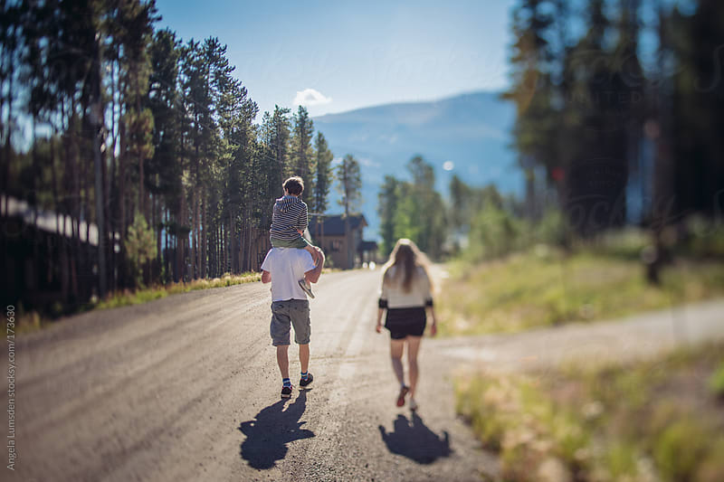 Family walking on a mountain road in summer by Angela Lumsden for Stocksy United