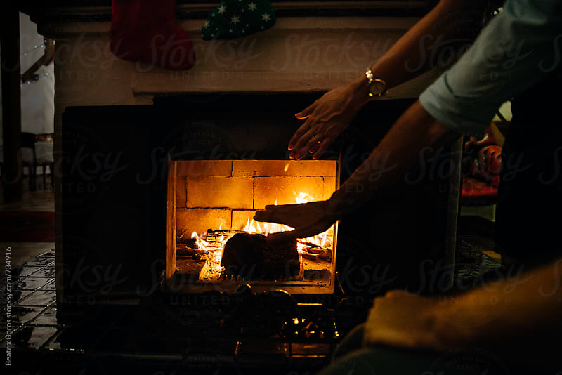 Couple's hands warming by the fire of the fireplace by Beatrix Boros for Stocksy United