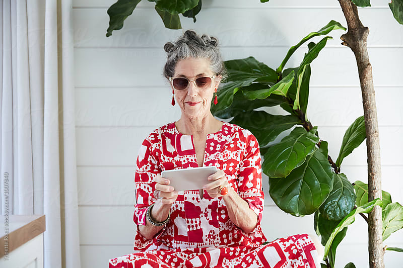 Stylish senior woman texting on mobile phone in her house by Trinette Reed for Stocksy United