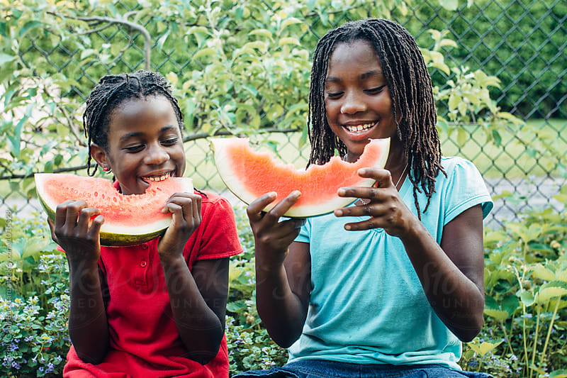 Two laughing African American girls eating watermelons by Gabriel (Gabi) Bucataru for Stocksy United