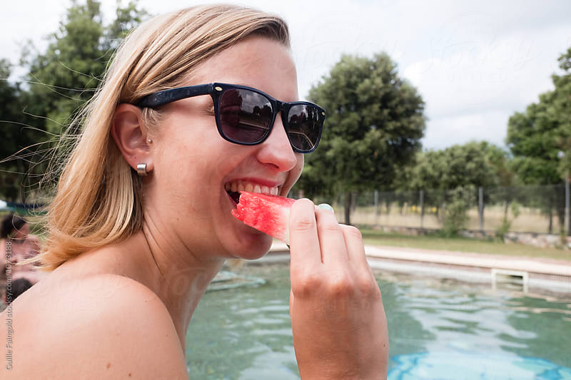 Smiling blonde eating watermelon at pool by Guille Faingold for Stocksy United