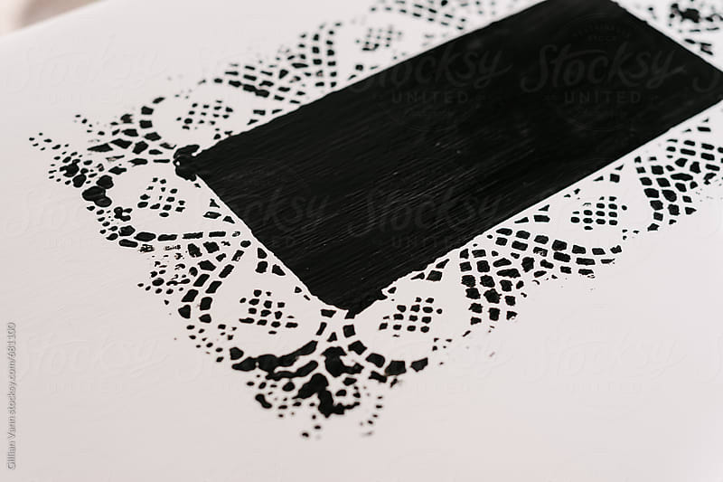 a stencil made with a doily and blackboard paint by Gillian Vann for Stocksy United