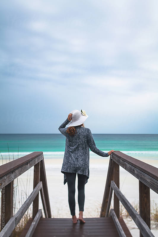 A woman wearing a hat standing on an empty beach with dark clouds. by RZ CREATIVE for Stocksy United