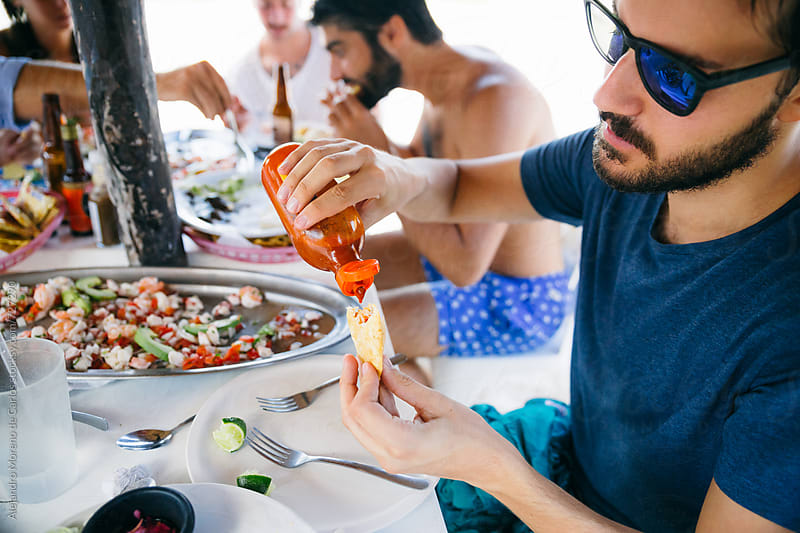 Man putting salsa to his empanada while enjoying Mexican food with a group of friends in a beach bar by Alejandro Moreno de Carlos for Stocksy United