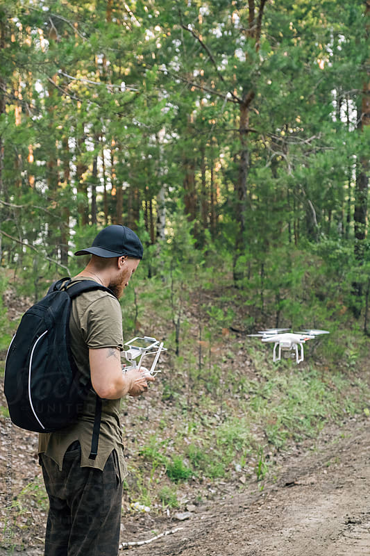 Back view of man using drone in forest by Danil Nevsky for Stocksy United