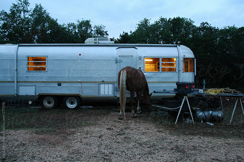 A scene that epitomizes Americana: a horse wandering towards a cozy lit trailer after dusk in rural Texas.  by Kaat Zoetekouw for Stocksy United