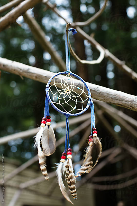 Dream catcher hanging on a wood structure at a trailer park by Carolyn Lagattuta for Stocksy United