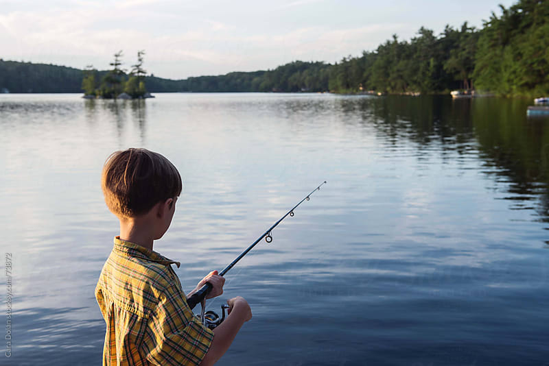 Boy fishing on a lake in the summer by Cara Dolan for Stocksy United