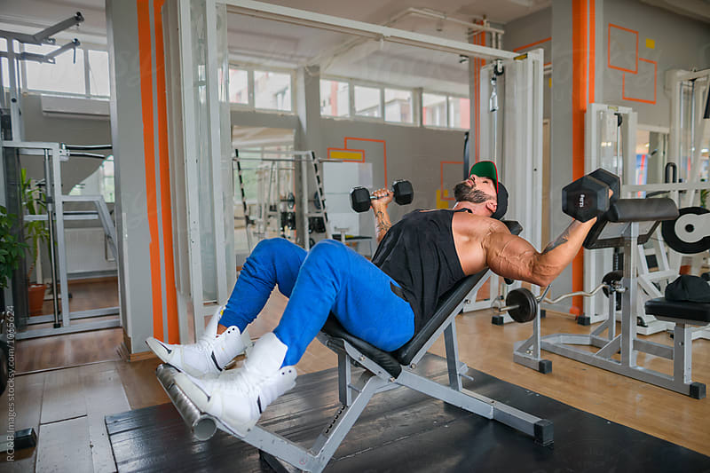 Bodybuilder working out chest muscles using dumbbells by RG&B Images for Stocksy United