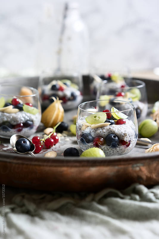 Chia seed,fruit puddings in glasses on a serving tray. by Darren Muir for Stocksy United