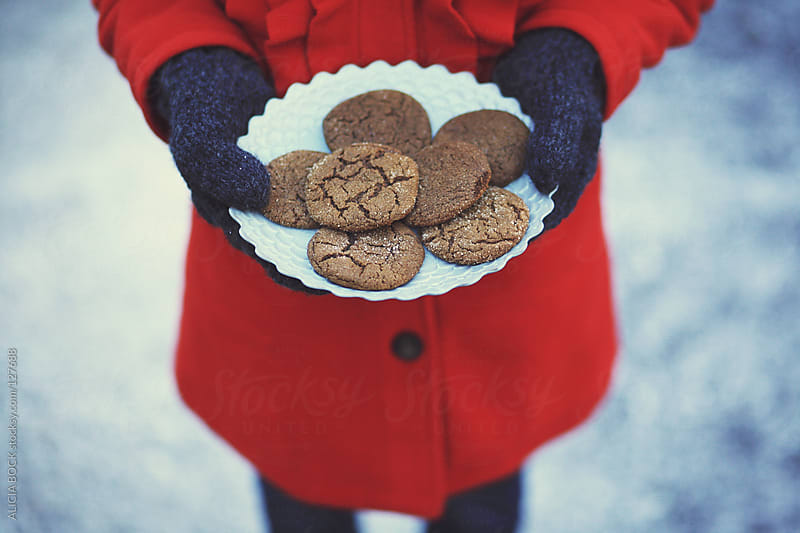 A Girls's Hands Wrapped In Warm Mittens Holding A Plate Of Cookies In The Snow by ALICIA BOCK for Stocksy United