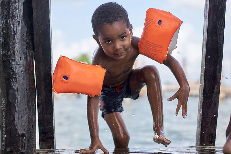 Young boy climbing up on dock after a swim in the ocean by Per Swantesson for Stocksy United