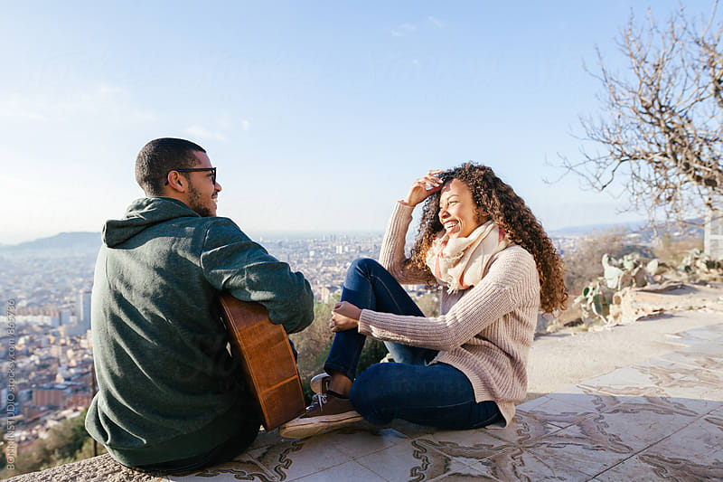 Man sitting playing guitar with his girlfriend above cityscape.  by BONNINSTUDIO for Stocksy United