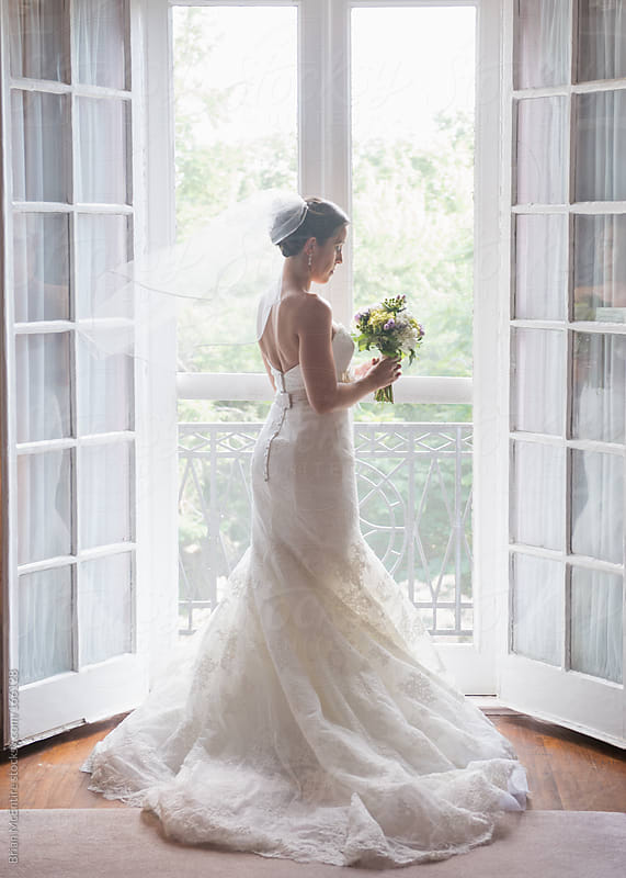 Bride Looking Near French Doors in Looking at Her Flower Bouquet by Brian McEntire for Stocksy United