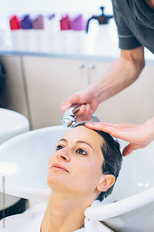 Hairdresser washing woman's hair by michela ravasio for Stocksy United