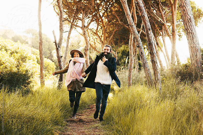 Happy hipster couple running in the forest. by BONNINSTUDIO for Stocksy United