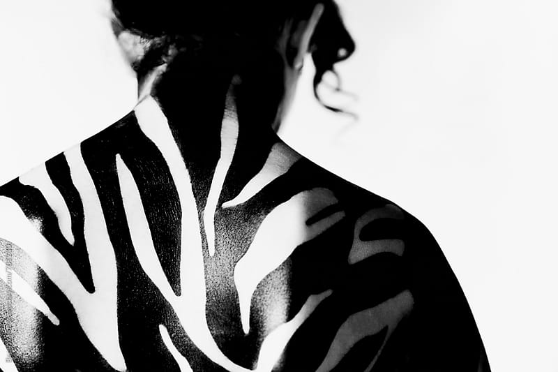 Woman's shoulders with zebra striped body paint in front of white background by Beatrix Boros for Stocksy United