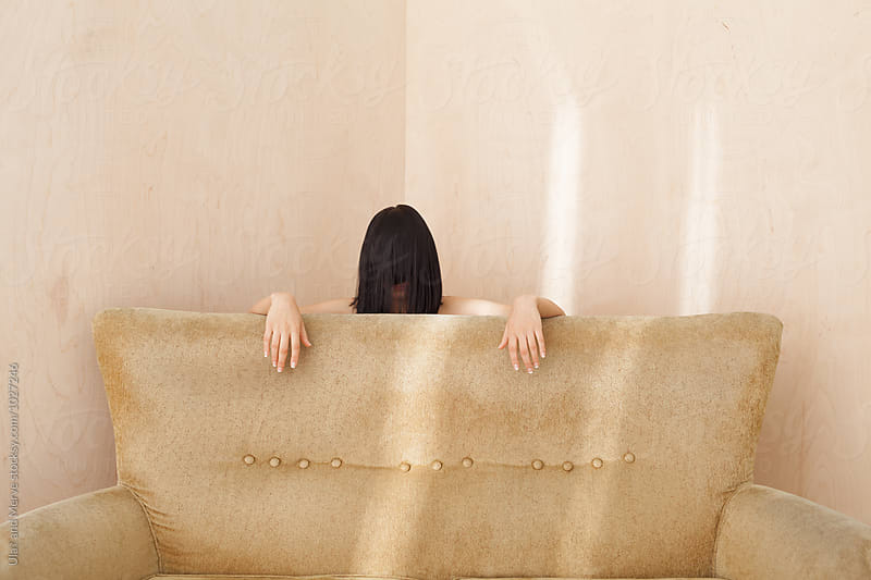 creepy lady behind a retro couch by Ulaş and Merve for Stocksy United