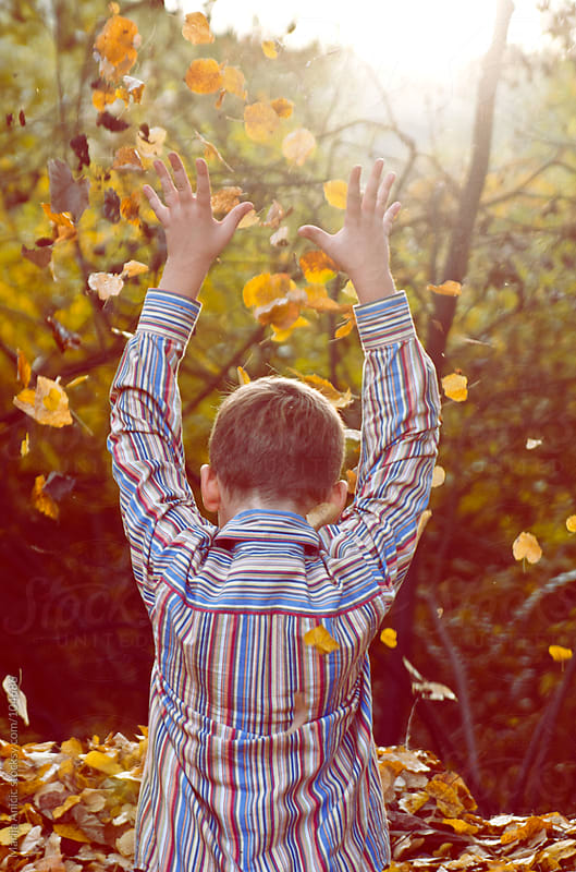 young boy is playing ,throwing autumn leaves  by Marija Anicic for Stocksy United