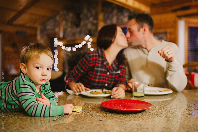 baby looks at camera while parents kiss at christmas by Kristin Rogers Photography for Stocksy United