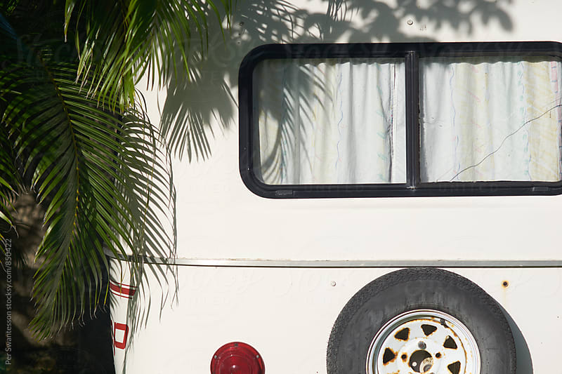 White parked vintage camper under a palm tree by Per Swantesson for Stocksy United