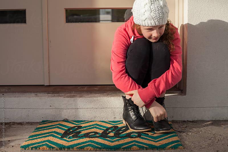 Girl at front door mat hello by skye torossian for Stocksy United
