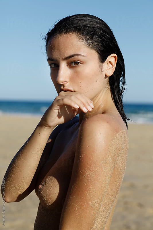 attractive naked young, attractive female on the beach by Rene de Haan for Stocksy United