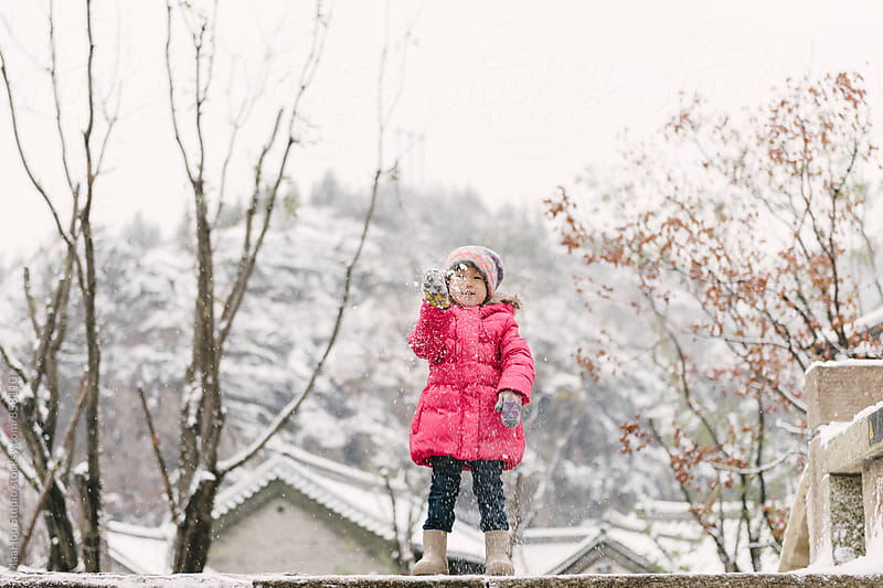 Baby girl playing with snow by Maa Hoo for Stocksy United