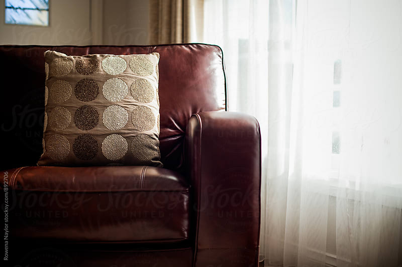 Comfy leather sofa with cushion by Rowena Naylor for Stocksy United