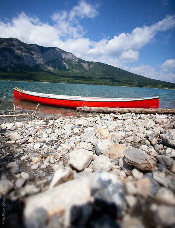 Red boat on a mountain lake by Mima Foto for Stocksy United