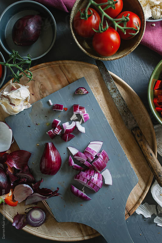 Sliced red onion on a cutting board surrounded by other vegetable ingredients on a table. by Darren Muir for Stocksy United