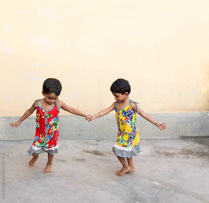 Twins play together by PARTHA PAL for Stocksy United