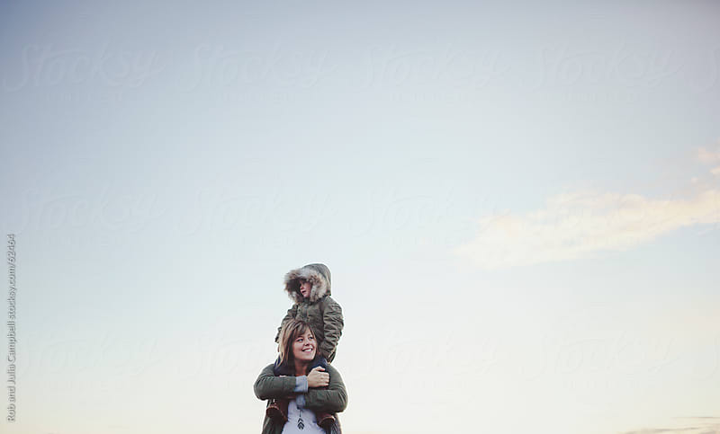 Mom gives three year old daughter shoulder ride near ocean by Rob and Julia Campbell for Stocksy United