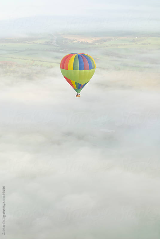 Hot Air Balloon Flying Over Foggy Valley by Adrian P Young for Stocksy United