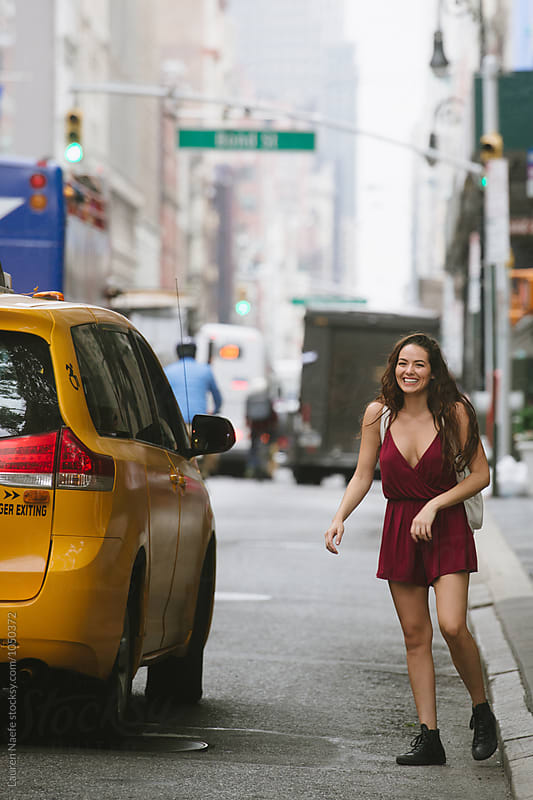 Young woman with cab in the city by Lauren Naefe for Stocksy United