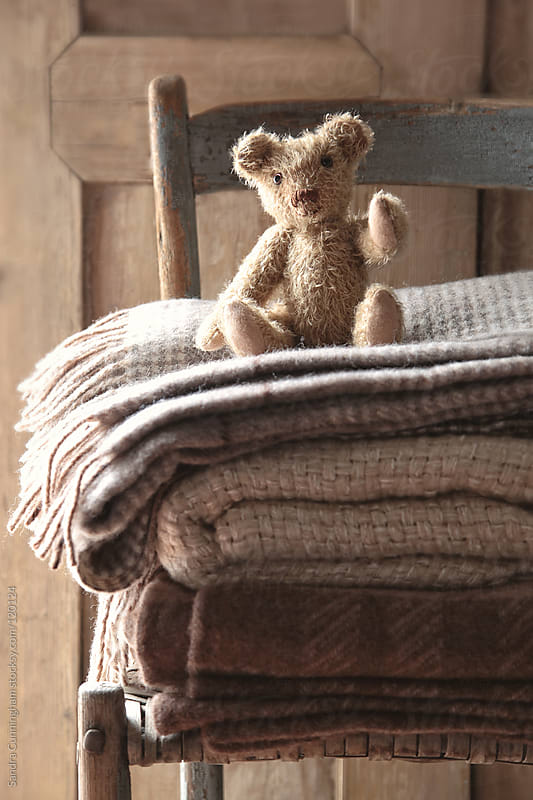 Small teddy bear on chair with wool blankets by Sandra Cunningham for Stocksy United