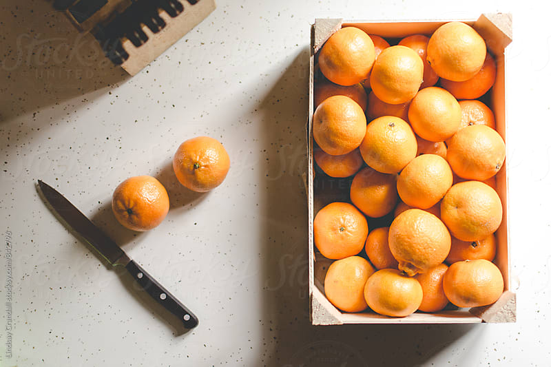 Small oranges in box with knife by Lindsay Crandall for Stocksy United