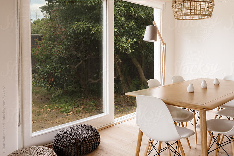 dining table with a view to an outside garden by Gillian Vann for Stocksy United