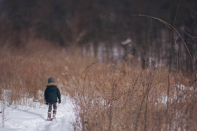 Young Boy Hiking Along a Snow Covered Trail by Kevin Keller for Stocksy United