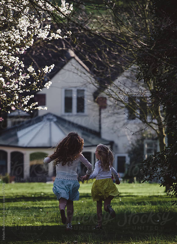 Two little girls running towards a house holding hands. by Helen Rushbrook for Stocksy United