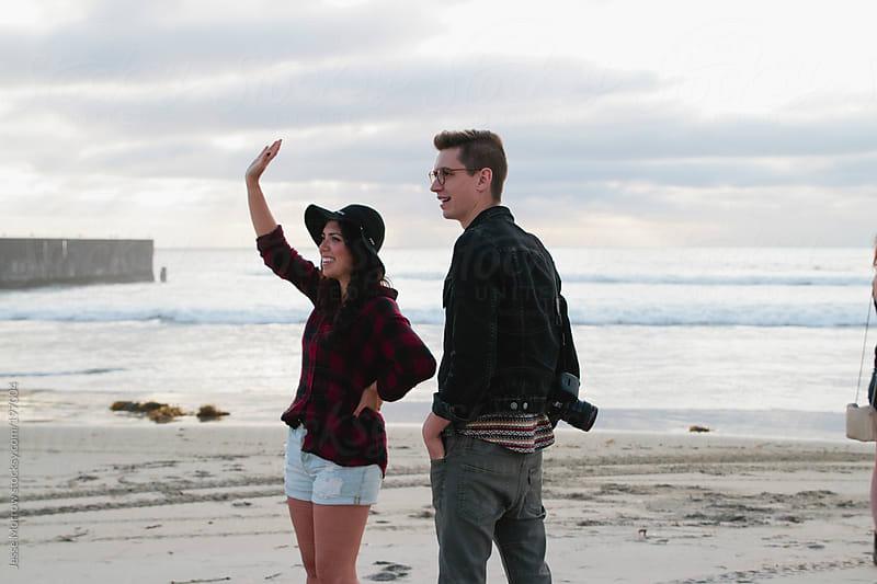 Couple walks along beach by Jesse Morrow for Stocksy United