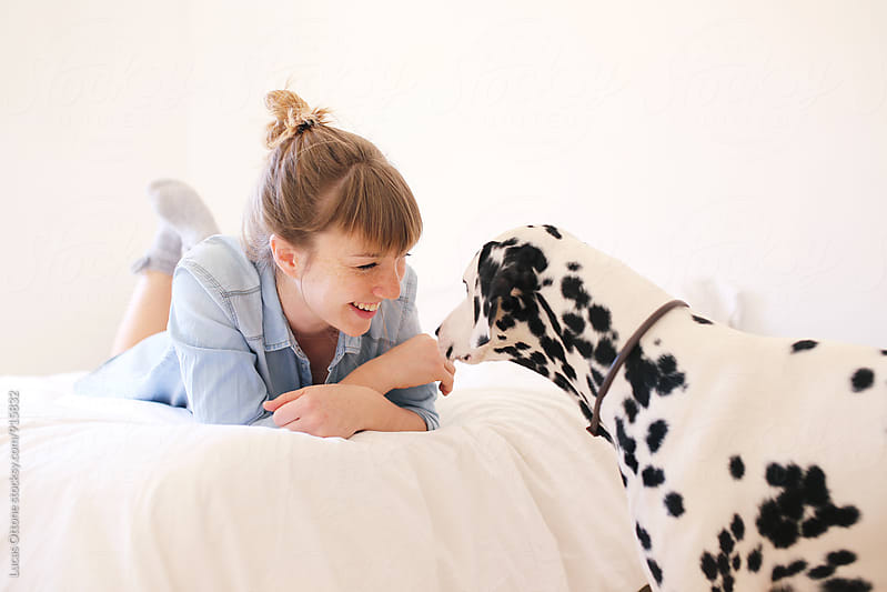 Girl on the bed smiling at a Dalmatian dog by Lucas Ottone for Stocksy United