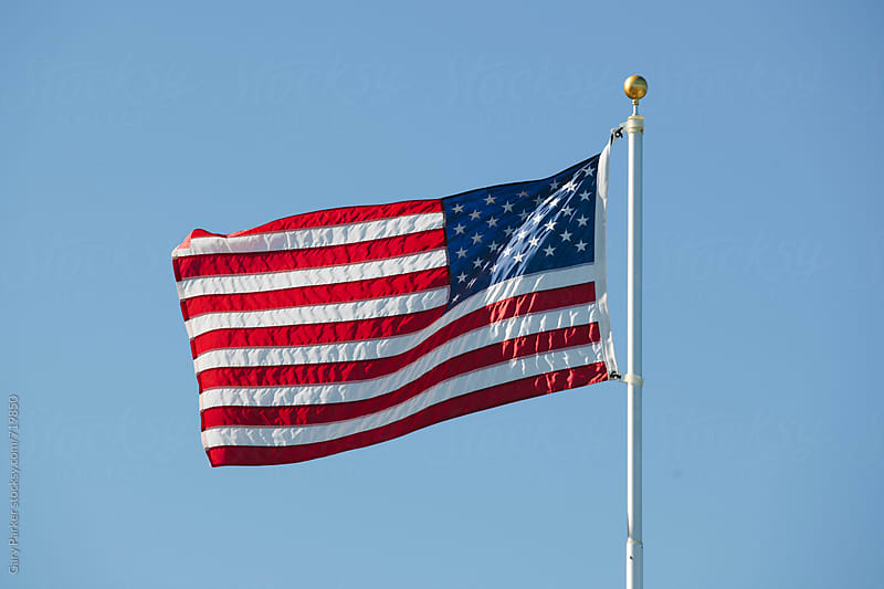The American Flag blowing in the wind on a sunny day by Gary Parker for Stocksy United