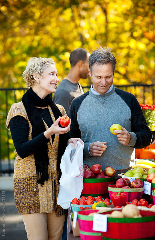 Farmer's Market: Man and Woman Selecting Apples by Sean Locke for Stocksy United